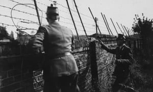 West Berlin police peer over the Berlin wall into eastern sector.