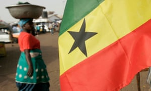 A woman selling food walks past a Ghanaian flag on sale at a stall in Tamale, northern Ghana