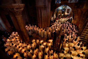 Latin Catholic clergymen hold candles as they circle the Anointing at the Church of the Holy Sepulchre in Jerusalem