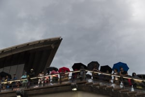 Crowds endured an early thunderstorm which passed before the midnight fireworks