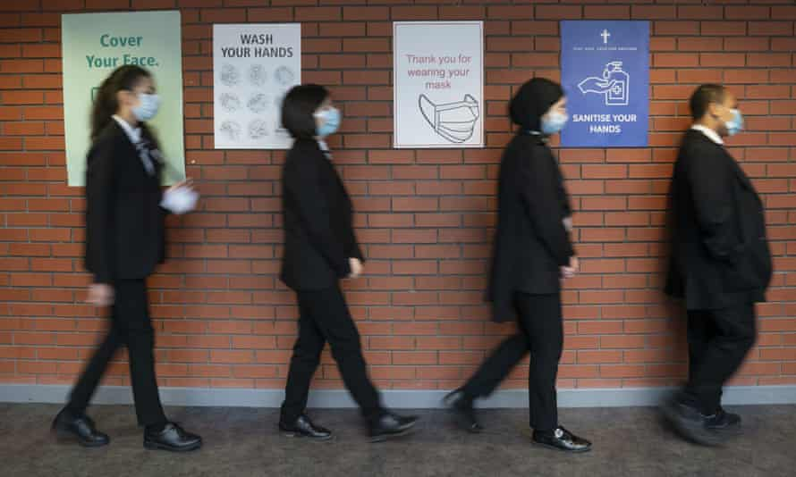 Pupils queue for a socially distanced assembly at a school in Manchester, England.