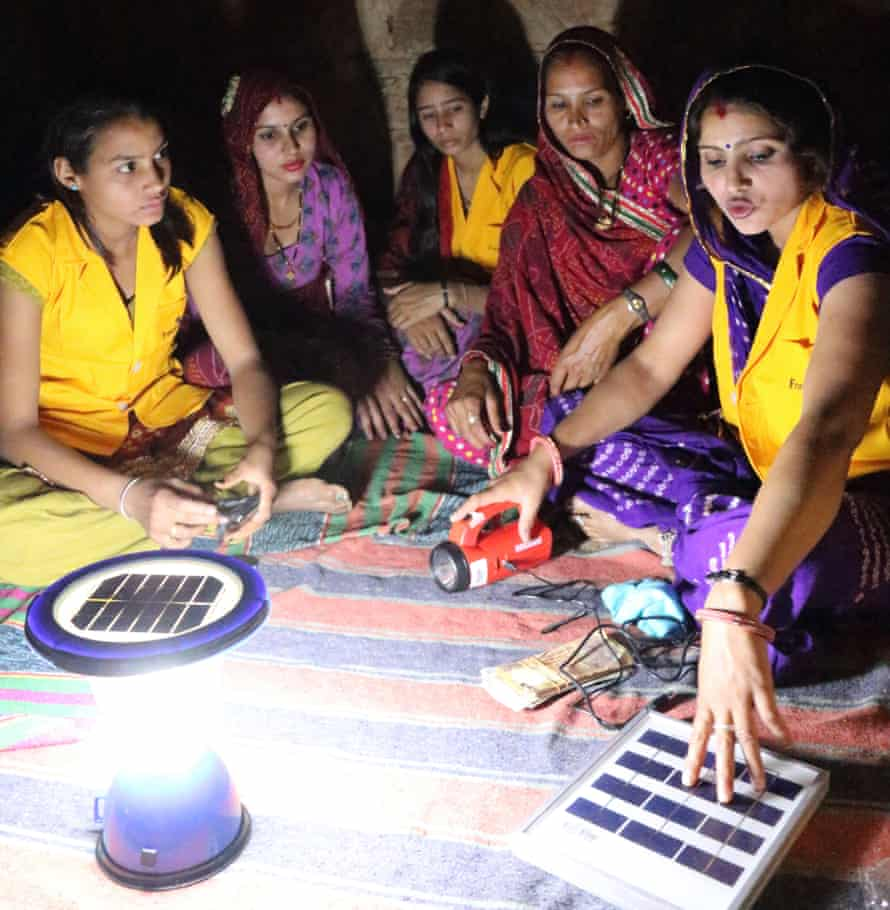 Hansa Chaudhary sitting with a group of women around a solar lamp