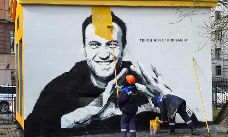 A worker paints over graffiti of the jailed Kremlin critic Alexei Navalny in Saint Petersburg last month. The inscription reads: 'The hero of the new times.'