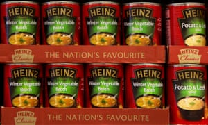 Tins of Heinz vegetable soup on a store shelf,