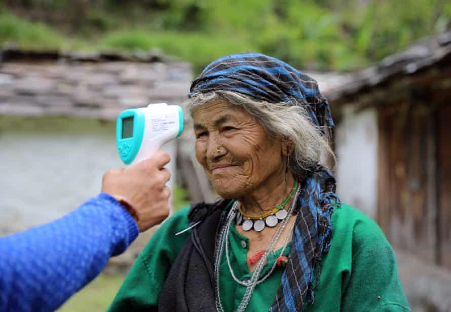 Baisakhi Devi, 90, has her temperature checked by a community health worker in Durmi.