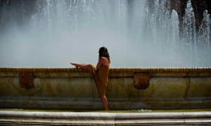 A woman cools off in a fountain