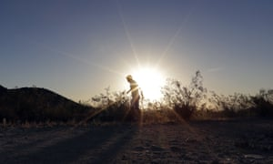 A man runs through the South Mountain Park at sunrise to avoid the excessive heat in Phoenix. A record heat wave is rolling into Arizona, Nevada and California.