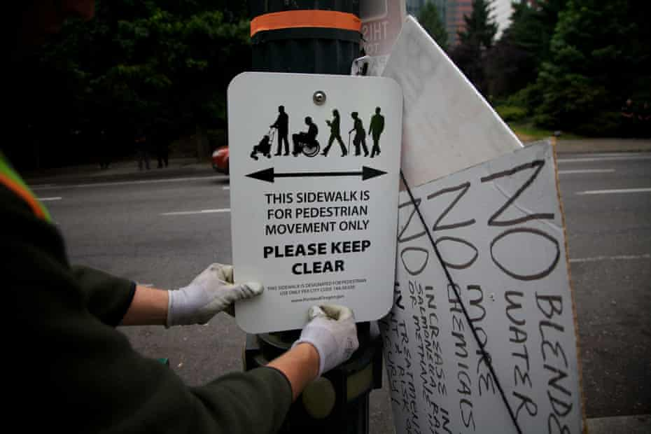 People from Portland Habilitation Center replace signs around Portland, Oregon.