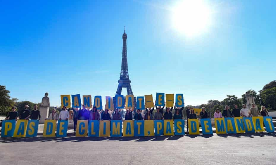 The Paris administrative court ruled in favour of four NGOs, seen here holding a banner reading 'candidates, no climate, no mandate' in front of the Eiffel Tower