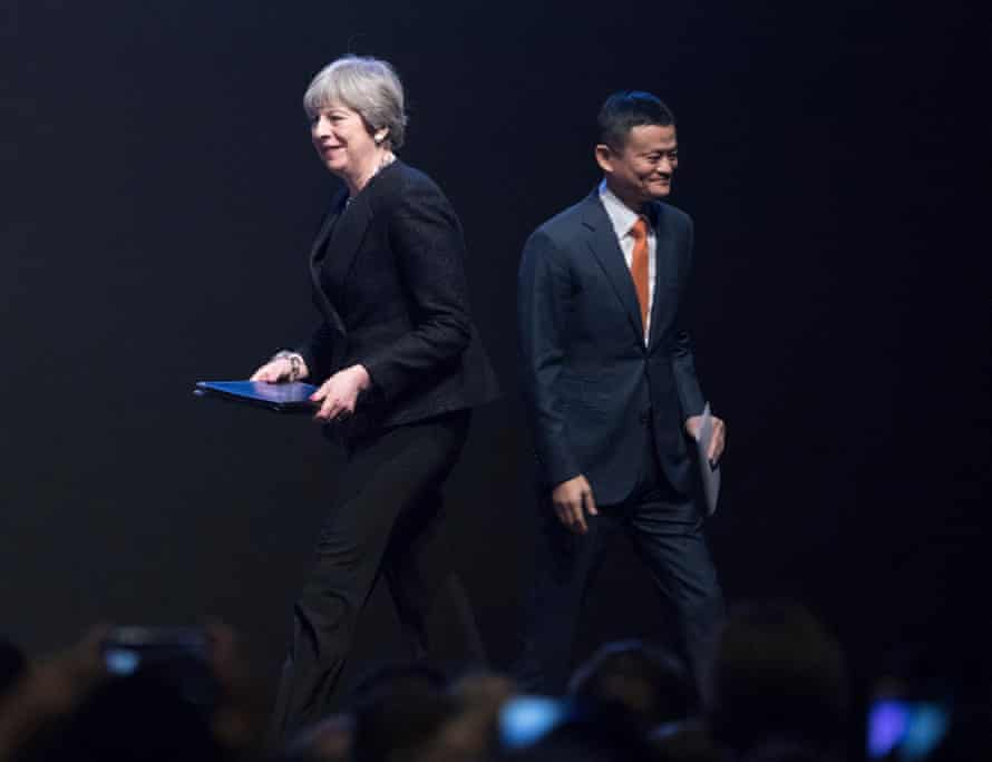 Theresa May passes Jack Ma, chairman of Alibaba Group Holding Ltd. as she walks on stage to speak at the China-Britain Business Forum