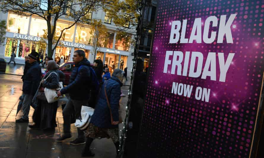 Shoppers walking past Black Friday sign on Oxford Street in London
