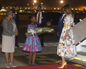 A flower girl and Margaret Kenyatta, Kenya's first lady, greet Trump on arrival at Jomo Kenyatta International airport, Nairobi
