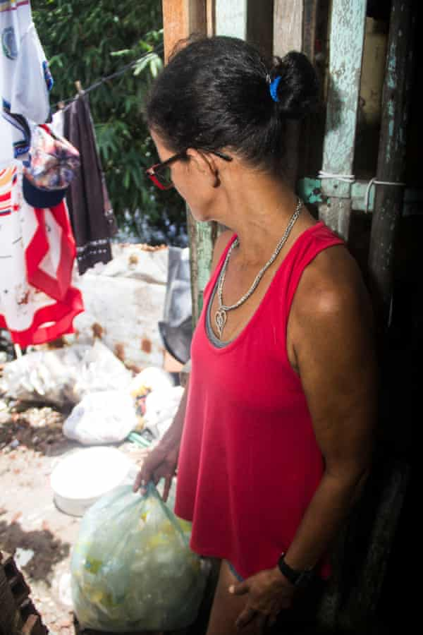 Maria das Gracas with bags of plastic waste she has collected from the Tejipió river