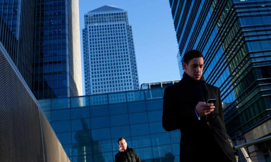 A worker looks at his phone at the Canary Wharf business district in London.