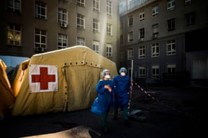 Health workers wearing face masks stand in front of a triage tent for suspected Covid-19 patients outside the Santa Maria hospital in Lisbon.
