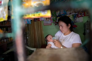 Jovelyn, 32, bottle feeds her five month-old baby JM in her home and shop in Caloocan City, Metro Manila, the Philippines.