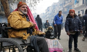 A man in a wheelchair eats as he waits to be evacuated from a rebel-held sector of eastern Aleppo, Syria.