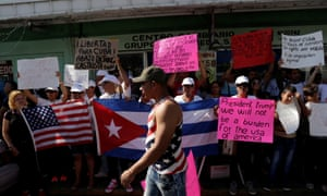 Cuban migrants stuck in Nuevo Laredo hold Cuban and American flags during a protest to ask the Mexican and the US governments to allow them to cross the border legally.