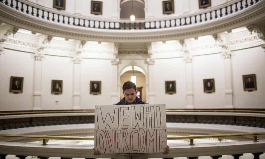 A man holds a sign inside the state capitol shortly after the electoral college cast their vote in Austin, Texas, putting Donald Trump over the 270 votes needed.