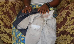 Ndoola holds the bloodstained shirt her eight-year-old son was wearing when he was kidnapped. Six days after the abduction he was released in a critical condition.