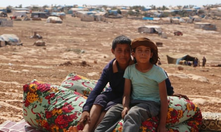 Displaced Syrian boys who fled from regime raids sit in a camp in Kafr Lusin near the border with Turkey.