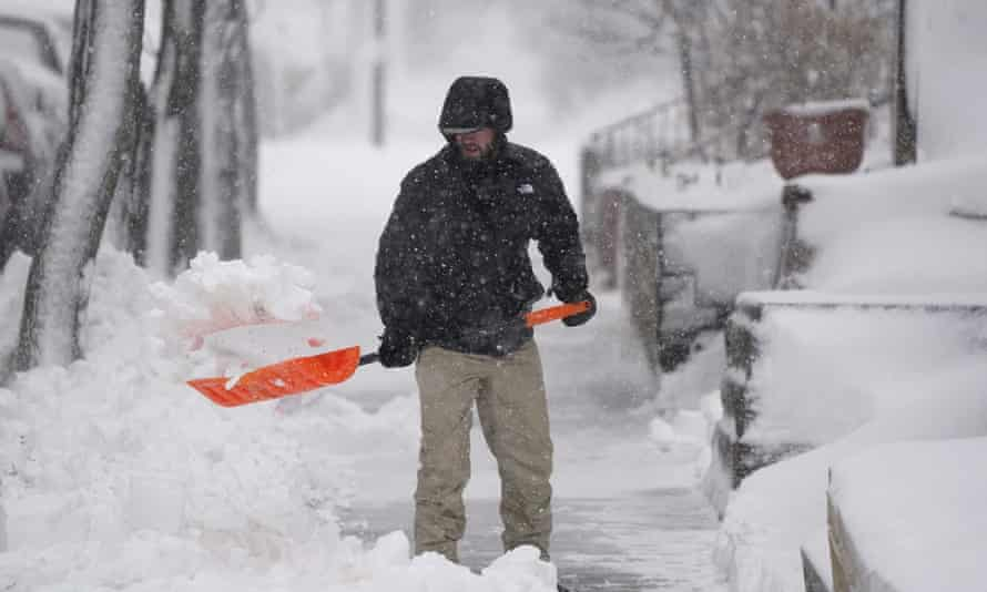 A man clears snow from the walkway of his home in Denver on Sunday.