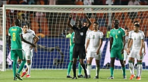 Referee Neant Alioum refers to VAR after awarding a penalty to Senegal.