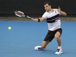 Grigor Dimitrov hits a forehand return to Pablo Cuevas.