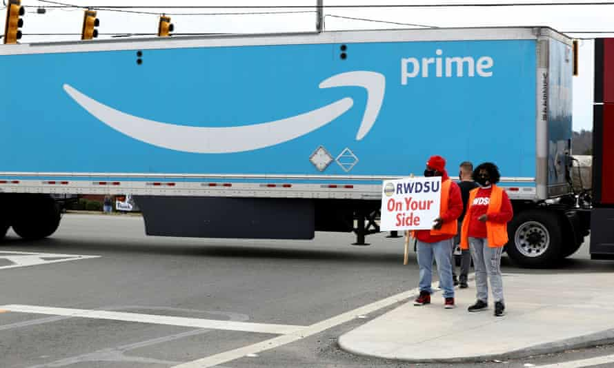 People hold a banner at the Amazon facility on 5 March as members of a congressional delegation arrive to show their support for workers who will vote on whether to unionize, in Bessemer, Alabama.
