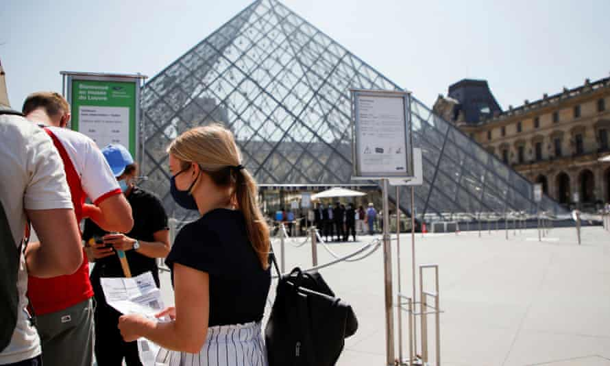 People with health passes wait to enter the Louvre museum in front of the Louvre Pyramid in Paris.