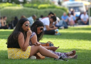 A sunbather eats an ice-cream at South Bank, south-east London, on the hottest September day since 1911