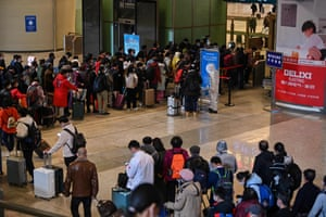 Mask-clad passengers wait in a line after arriving at the railway station in Wuhan
