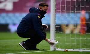 A member of ground staff disinfects the goal posts at Villa Park