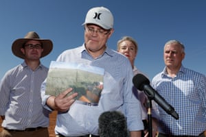 Australian Prime Minister Scott Morrison (C) holds up a photo from February 2016 of what sheep and cattle graziers Stephen and Annabel Tully's property used to look like