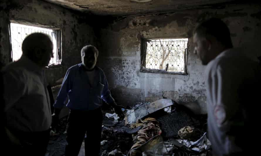 Palestinians inspect a house set on fire in a suspected attack by Jewish extremists yesterday.