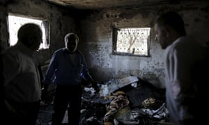 Palestinians inspect fire damage at a house in Duma.
