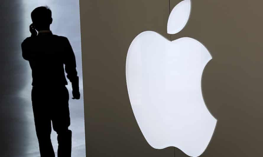 A man talking on his smartphone walks into an Apple store