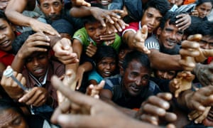 Rohingya refugees stretch out their hands to receive aid distributed at a makeshift camp in Cox's Bazar, Bangladesh