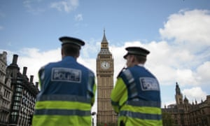 British police officers stand in front of the Houses of Parliament in central London