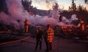 Firefighters mop up a burned down home destroyed by the Hillside fire in San Bernardino, 31 October 2019.