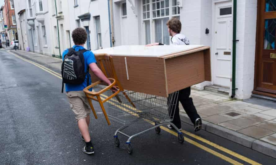 Two students people men moving furniture wheeling a wardrobe on a shopping trolley aberystwyth wales ukD5GK94 Two students people men moving furniture wheeling a wardrobe on a shopping trolley aberystwyth wales uk