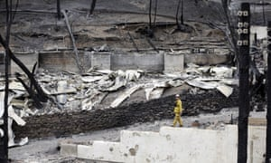 A firefighter walks below the scorched hillside and buildings at Harbin Hot Springs resort after a wildfire.