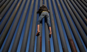 A migrant, part of a caravan of thousands from Central America, climbs the border fence between Mexico and the US in Tijuana on 18 November 2018