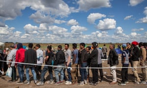 Refugees at the Röszke crossing on the Serbian-Hungarian border wait to board a bus to take them to a detention centre.