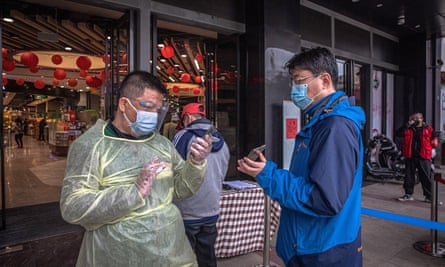 A worker in a protective outfit checks health QR codes of a man at the entrance of a shopping mall in Wuhan