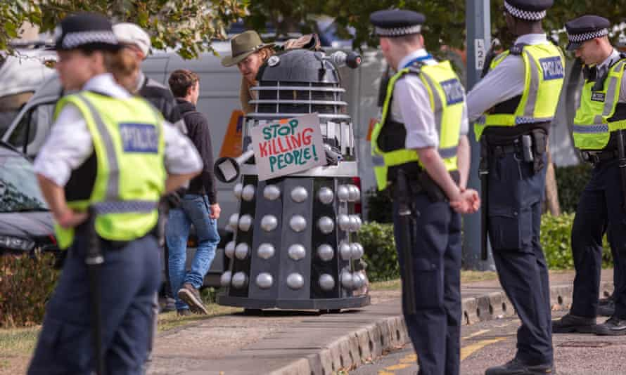 Police at a protest against the DSEI arms fair, looking at protester in dalek costume with sign reading: 'Stop killing people!'