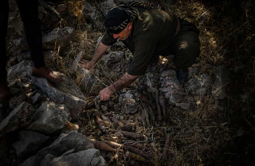 Rizgar Ali examines a mortar shell and RPG cache hidden behind a defensive wall in Serdera Village near Penjwen, Iraqi Kurdistan. The defensive wall and the explosives are Iraq-Iran War remnants.