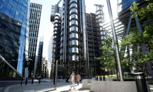 A woman wearing a protective face mask passes Lloyd's building in London.