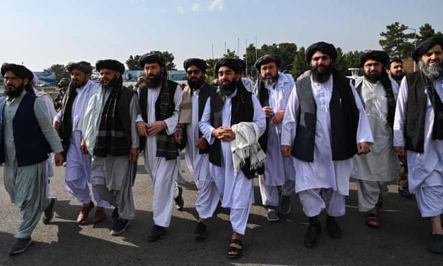 Group of more than a dozen men in a line wearing Islamic dress