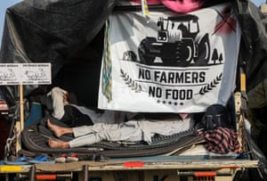 Farmers rest inside their truck during the protest at Singhu